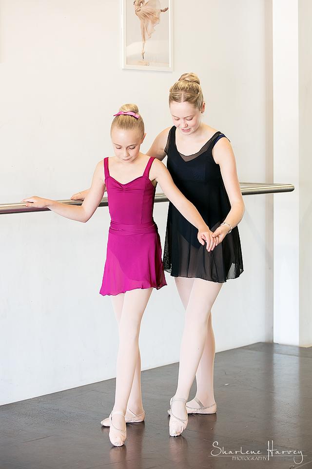 Teacher assisting ballet student